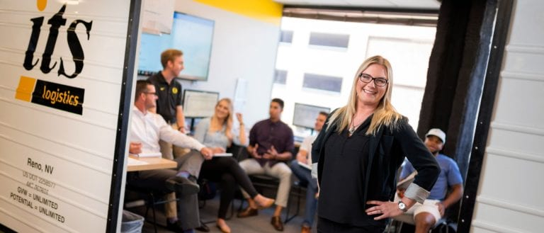 featured image female employee standing in front of the ITS Logistics team in the Reno office