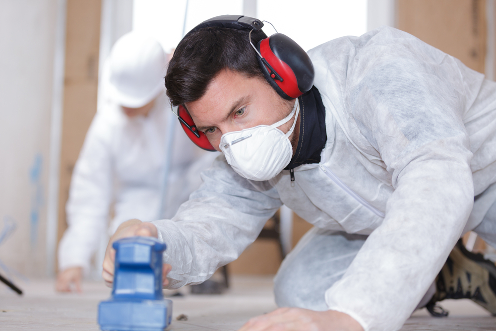 featured image showing a man sanding wood while wearing ppe