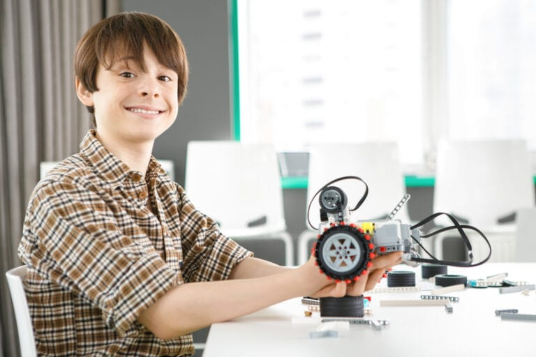 featured image showing Excited young boy smiling to the camera holding a robot he is building