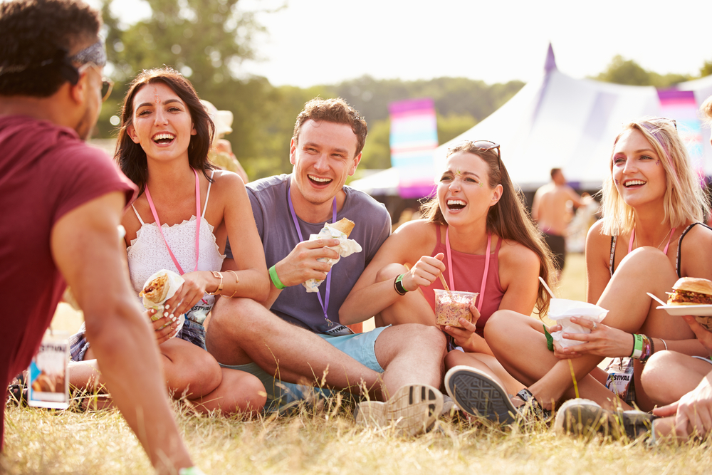 featured image showing friends sitting on the grass and eating food at a festival