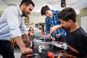 Featured image showing a teach with two male students building a robot in the classroom
